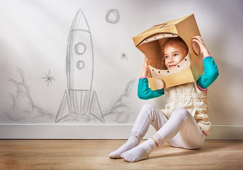 Child playing astronaut with paper